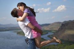 Pares que se besan en montañas Imagen de archivo