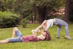 Pares que se besan inusuales jovenes al aire libre en el parque, en la posición extrema Fotos de archivo libres de regalías