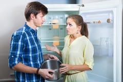 Pares que se colocan cerca de estantes vacíos del refrigerador Imagen de archivo libre de regalías