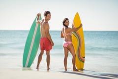 Pares que se colocan con la tabla hawaiana en la playa Imagen de archivo