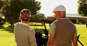 Pares que se colocan en el campo de golf que mira alrededor metrajes