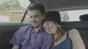 Pares que se colocan en el coche del asiento trasero que se divierte y que mira el contenido social de los medios en tecnología y almacen de metraje de vídeo
