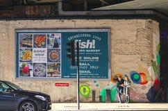 Pares que se colocan en la acera delante de la muestra que hace publicidad de pescados en el mercado de la ciudad con arte en la  imágenes de archivo libres de regalías
