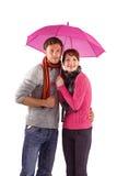 Pares que se colocan por debajo un paraguas Foto de archivo libre de regalías