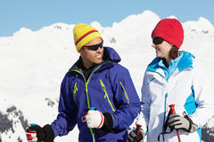 Pares que se divierten el día de fiesta del esquí en montañas fotografía de archivo libre de regalías