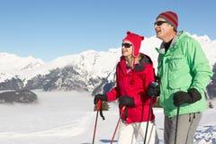 Pares que se divierten el día de fiesta del esquí en montañas Fotografía de archivo