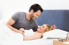 Pares que se divierten en cama Imagenes de archivo
