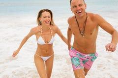 Pares que se divierten en la playa Imagen de archivo
