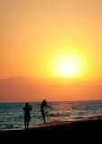 Pares que se divierten en la playa en la puesta del sol Foto de archivo libre de regalías