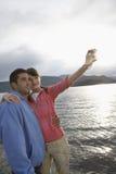 Pares que se fotografían en la playa Imágenes de archivo libres de regalías