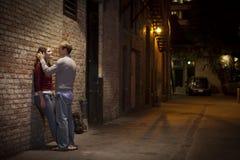 Pares que se inclinan contra la pared de ladrillo de la manera del callejón Foto de archivo