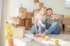 Pares que se mueven en nuevo hogar El sentarse en piso y relajación después de desempaquetar Hacer el selfie con smartphone fotos de archivo