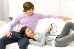 Pares que se reclinan sobre el sofá Imágenes de archivo libres de regalías
