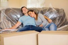 Pares que se reclinan sobre el sofá Fotos de archivo libres de regalías