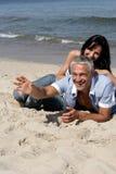Pares que se reclinan sobre la playa Imagen de archivo