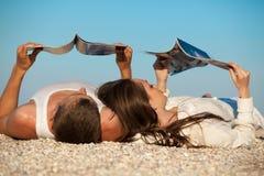 Pares que se reclinan sobre la playa Fotografía de archivo