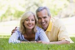 Pares que se relajan al aire libre en la sonrisa del parque Foto de archivo