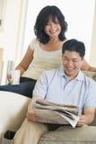 Pares que se relajan con un periódico y una sonrisa Imagen de archivo