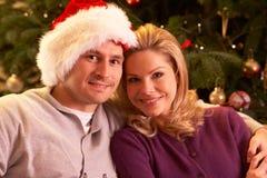 Pares que se relajan delante del árbol de navidad Fotos de archivo libres de regalías