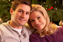 Pares que se relajan delante del árbol de navidad Foto de archivo libre de regalías