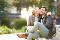 Pares que se relajan en banco de parque con café para llevar fotografía de archivo libre de regalías