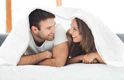 Pares que se relajan en cama Foto de archivo