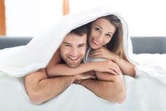 Pares que se relajan en cama Foto de archivo libre de regalías