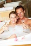 Pares que se relajan en el baño que bebe a Champagne Together Fotografía de archivo