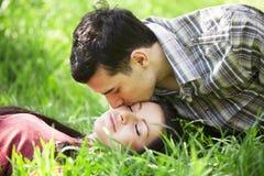 Pares que se relajan en hierba verde Imágenes de archivo libres de regalías