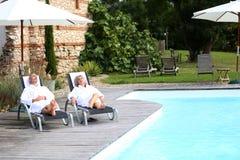 Pares que se relajan en la cubierta de la piscina de la piscina Fotos de archivo libres de regalías