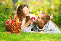 Pares que se relajan en la hierba y que comen manzanas Foto de archivo libre de regalías