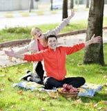 Pares que se relajan en la hierba y que comen manzanas fotografía de archivo