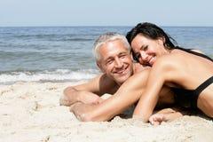 Pares que se relajan en la playa Imagen de archivo