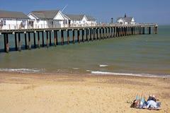 Pares que se relajan en la playa, Inglaterra Imágenes de archivo libres de regalías