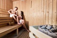 Pares que se relajan en la sauna Imagen de archivo libre de regalías