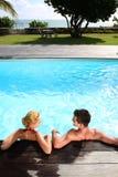 Pares que se relajan en piscina Foto de archivo libre de regalías