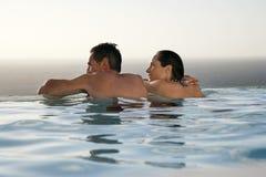 Pares que se relajan en piscina del infinito en el centro turístico Foto de archivo