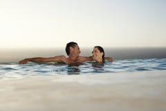 Pares que se relajan en piscina del infinito en el centro turístico Imagen de archivo