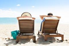 Pares que se relajan en sillas de cubierta en el complejo playero Imágenes de archivo libres de regalías