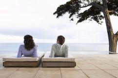 Pares que se relajan en Sunbeds por la piscina del infinito Foto de archivo libre de regalías