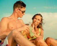 Pares que se relajan en una playa Foto de archivo libre de regalías