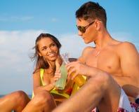 Pares que se relajan en una playa Imagen de archivo libre de regalías