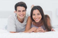 Pares que se relajan junto en cama Foto de archivo libre de regalías