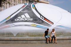 Pares que se sientan cerca de la bola 2012 del EURO Foto de archivo libre de regalías