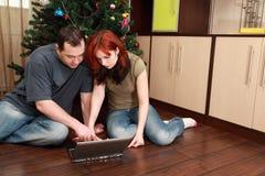 Pares que se sientan cerca del árbol de navidad con la computadora portátil Foto de archivo