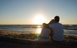 Pares que se sientan cerca del mar en puesta del sol Fotografía de archivo libre de regalías