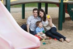 Pares que se sientan con su hijo en patio Fotos de archivo libres de regalías