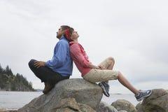 Pares que se sientan de nuevo a la parte posterior en rocas contra el océano Foto de archivo libre de regalías