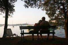 Pares que se sientan en banco en la puesta del sol Fotos de archivo libres de regalías