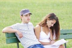 Pares que se sientan en banco en verano Imágenes de archivo libres de regalías